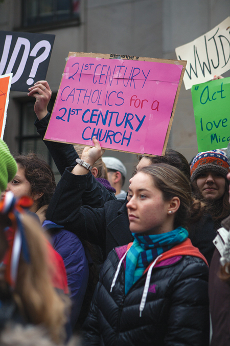 Students from Seattle Catholic schools join with other pro-LGBT demonstrators at a rally in front of the Archdiocese of Seattle to protest the firing of vice principal Mark Zmuda for marrying his same-sex partner. © ALEX GARLAND/DEMOTIX/CORBIS